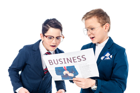 schoolboys pretending to be businessmen reading newspaper Isolated On White