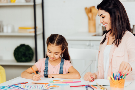 happy woman looking at cheerful daughter drawing and smiling at home