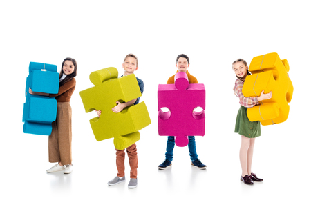happy kids looking at camera and holding jigsaw puzzle pieces on white