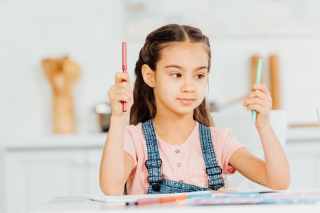 cute kid choosing between turquoise and red felt pens at home