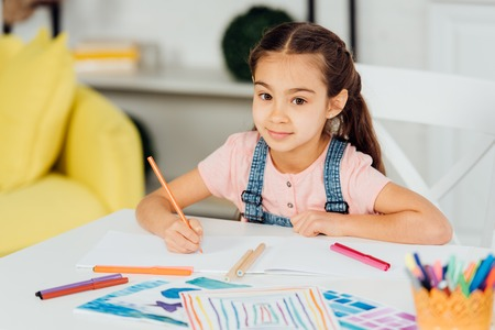 selective focus of happy child looking at camera while holding color pencil near paper at home
