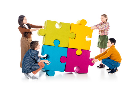 happy kids playing with jigsaw puzzle pieces on white Stock Photo