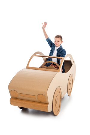 smiling boy sitting in cardboard car and waving on white Banco de Imagens