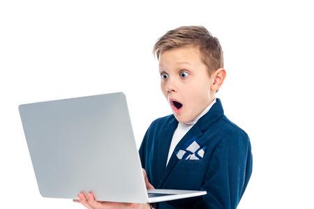 scolaro scioccato in tuta da uomo d'affari utilizzando laptop isolato su bianco