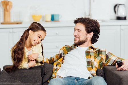 cheerful father sitting on sofa and holding remote controller near smiling daughter