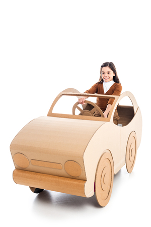 happy kid playing with cardboard car on white with copy space Фото со стока