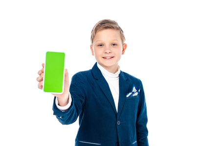 smiling schoolboy in formal wear presenting smartphone with green screen Isolated On White Stock Photo