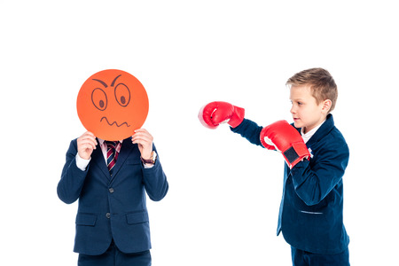 schoolboy holding angry face expression card while other schoolboy boxing in boxing gloves Isolated On White Stok Fotoğraf