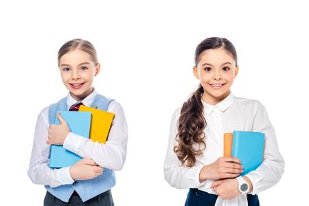 Gelukkige schoolmeisjes in formele kleding met boeken kijken naar camera geïsoleerd op wit Stockfoto