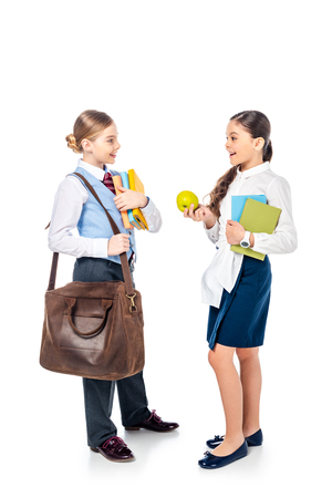 schoolgirls in formal wear with books and apple looking at each other and talking On White