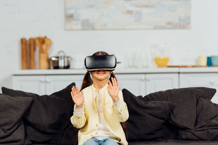 cheerful kid gesturing while wearing virtual reality headset at home