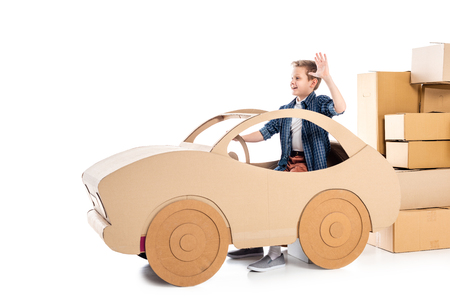 boy sitting in cardboard car and waving on white