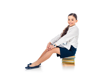 smiling schoolgirl in formal wear sitting on books and looking at camera On White with copy space