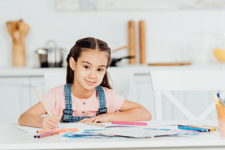 cute kid looking at camera while holding color pencil near paper at home