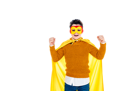 happy boy in superhero costume cheering with clenched fists Isolated On White