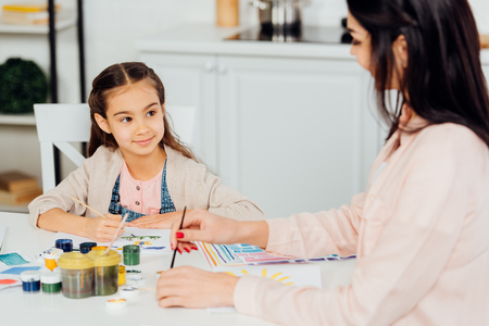selective focus of happy kid looking at mother holding paintbrush