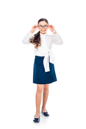 adorable schoolgirl in formal wear and glasses looking at camera and smiling Isolated On White
