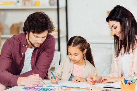 happy mother drawing near cute daughter and husband at home