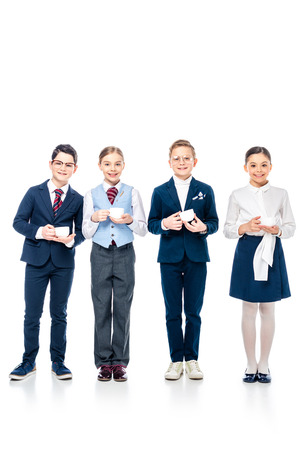 smiling schoolchildren pretending to be businesspeople holding coffee cups and looking at camera On White