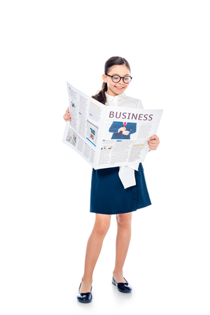 adorable schoolgirl in formal wear and glasses reading business newspaper On White
