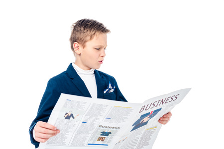 confused schoolboy in formal wear reading business newspaper Isolated On White 스톡 콘텐츠