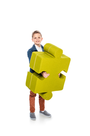 happy boy with jigsaw puzzle piece looking at camera on white Stock Photo