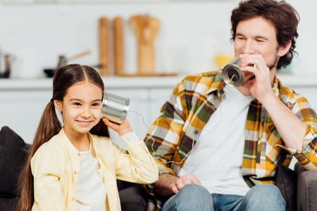 glücklicher Vater, der weiter spricht, kann telefonieren und fröhliche Tochter, die zu Hause zuhört Standard-Bild