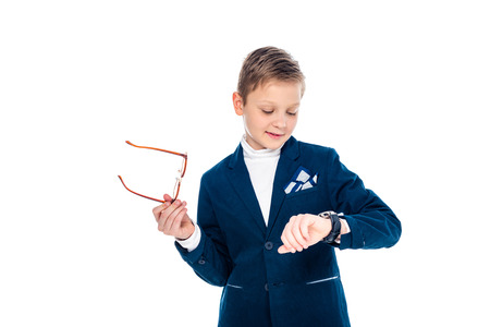 schoolboy in businessman suit holding glasses and looking at watch Isolated On White