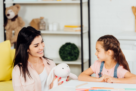cheerful mother holding soft toy near cute daughter at home
