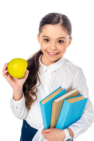 smiling schoolgirl holding apple and books while looking at camera Isolated On White
