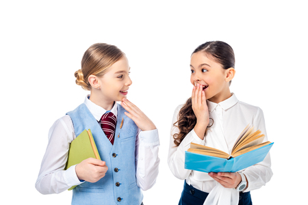 schoolgirls in formal wear with books covering mouth and Gesturing Isolated On White