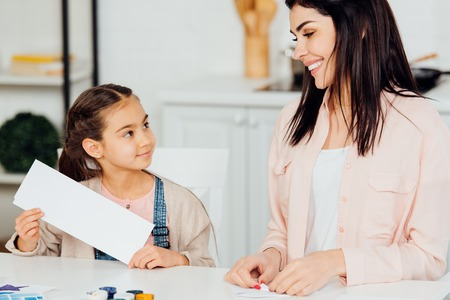 cheerful kid looking at happy mother  and holding blank paper