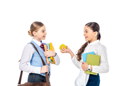 schoolgirls in formal wear with books and apple talking Isolated On White
