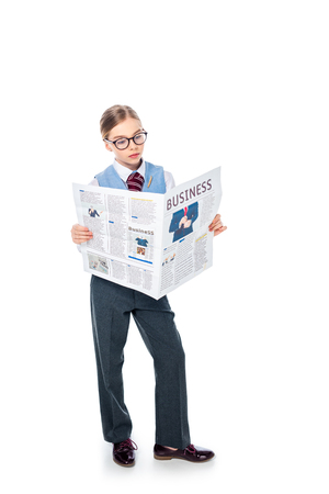 adorable schoolgirl in formal wear and glasses reading business newspaper On White Banco de Imagens - 122814813