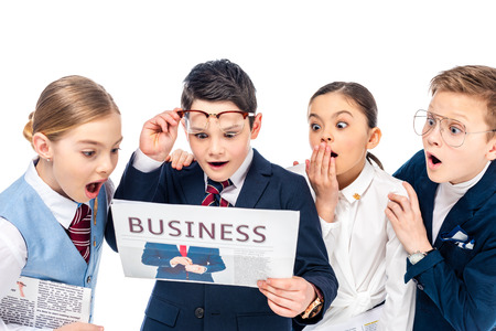 shocked schoolchildren pretending to be businesspeople reading newspaper Isolated On White