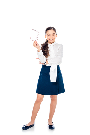 adorable smiling schoolgirl in formal wear holding glasses and posing On White 版權商用圖片 - 122815079