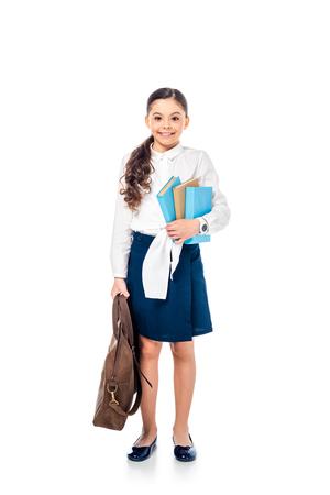 Schulmädchen in formeller Kleidung, das in die Kamera schaut und Bücher mit Tasche auf Weiß hält