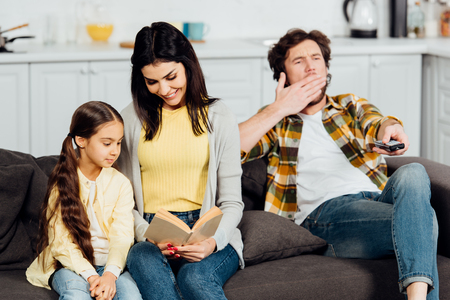 happy mother reading book to cute daughter near husband yawning on sofa