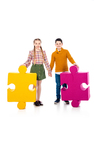 happy kids with jigsaw puzzle pieces holding hands on white