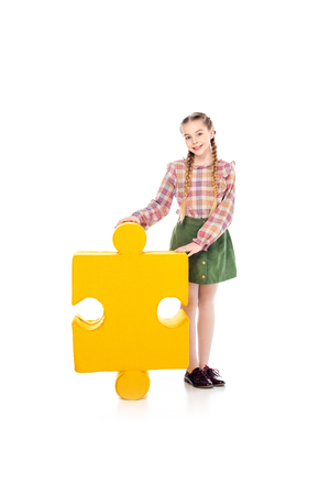 smiling kid with jigsaw puzzle piece looking at camera on white 版權商用圖片