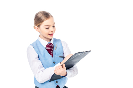 adorable schoolgirl in formal wear writing in clipboard Isolated On White with copy space Stockfoto - 122815279