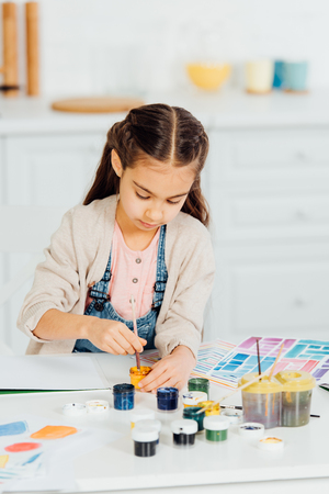 cute kid looking at yellow paint while holding paintbrush at home