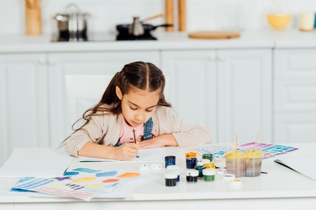 concentrated and cute kid painting on paper at home