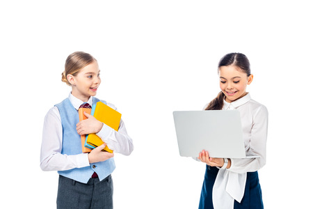 smiling schoolchildren in formal wear using laptop and holding books Isolated On White