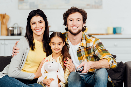 cheerful kid holding soft toy and sitting near happy parents at home