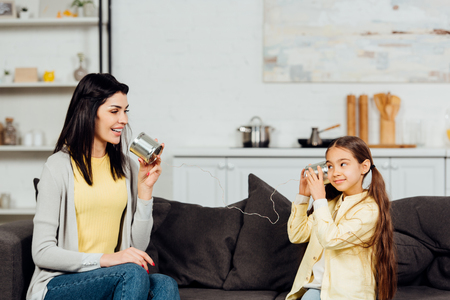 cheerful mother talking while holding tin can and playing with happy daughter