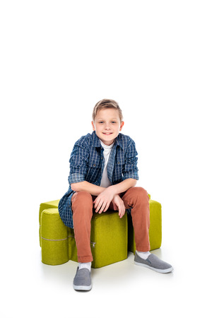 happy boy sitting on jigsaw puzzle pouf and looking at camera on white Stock Photo