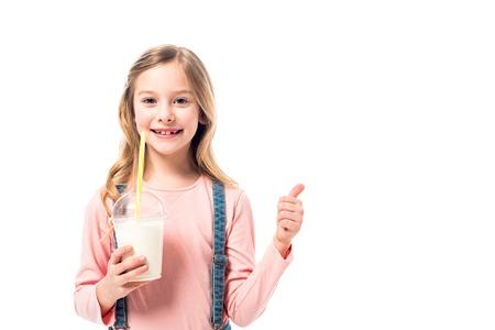 Smiling kid holding milkshake and showing thumb up isolated on white background