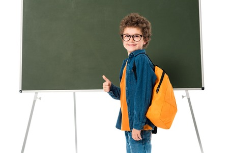 Smiling schoolboy in glasses standing near blackboard and showing thumb up isolated on white background