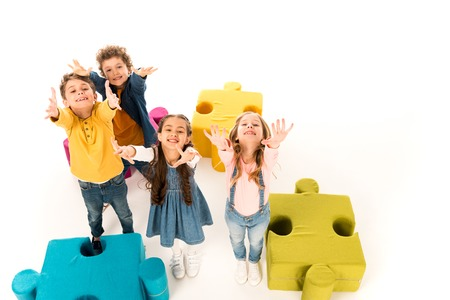 Overhead view of kids with outstretched hands near colorful jigsaw puzzles on white background